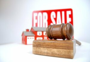 House auction concept shot with a sign, home and gavel
